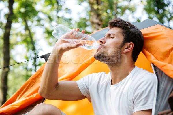 Attractive man tourist sitting and drinking water in touristic tent Stock photo © deandrobot