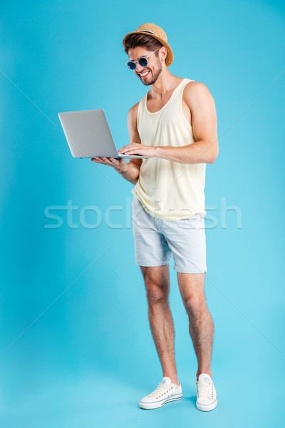 Full length of happy young man standing and using laptop Stock photo © deandrobot