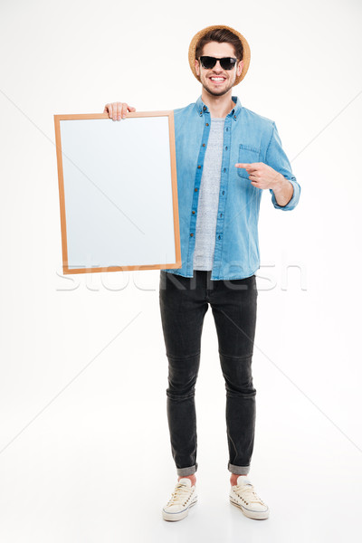 Happy young man holding blank whiteboard and pointing on it Stock photo © deandrobot