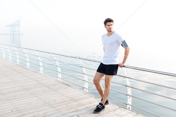 Man athlete with armband and cell phone standing on pier Stock photo © deandrobot