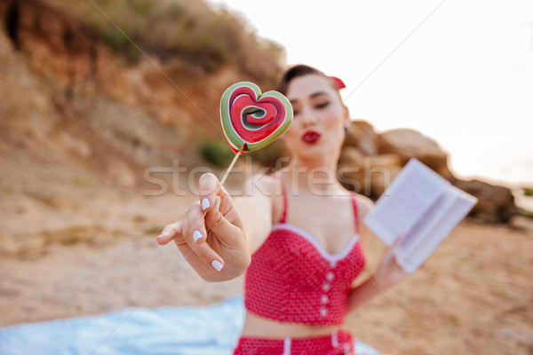 Pin up girl showing heart shaped candy at the beach Stock photo © deandrobot
