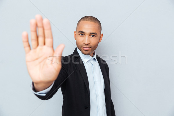 Young african man showing stop sign with hand Stock photo © deandrobot