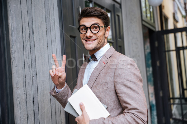 Young nerd man in eyeglasses showing v sign Stock photo © deandrobot