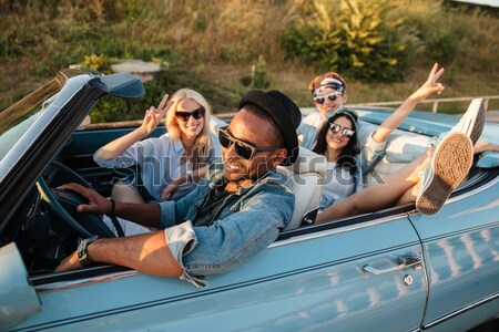 Happy young friends taking selfie with cell phone in car Stock photo © deandrobot