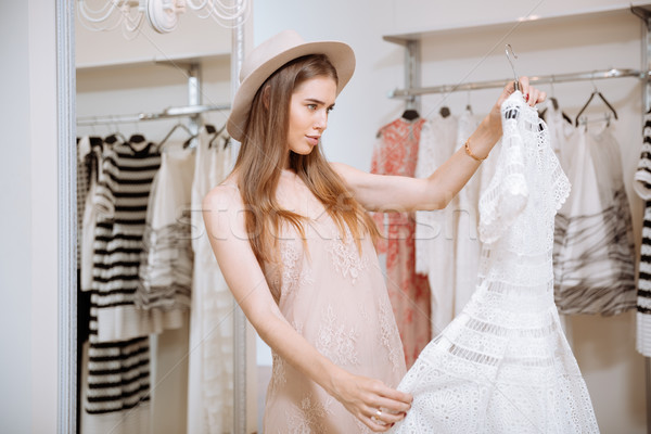 Woman looking at white dress and thinking in clothing store Stock photo © deandrobot