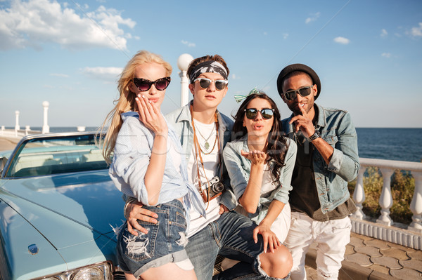 Happy young people standing and sendng kisses near vintage cabriolet Stock photo © deandrobot