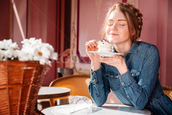 Happy woman eating sweet tasty cupcake in outdoor cafe Stock photo © deandrobot