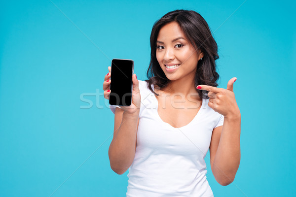 Young vietnamese woman pointing finger on blank smartphone screen Stock photo © deandrobot