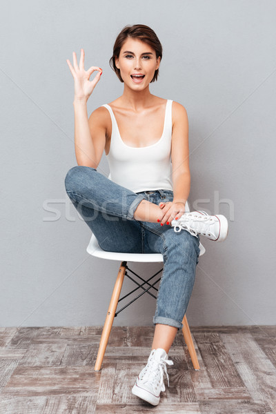 Attractive woman sitting on the chair and showing okay sign Stock photo © deandrobot