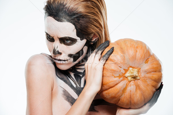 Portrait of girl with fearful halloween makeup holding pumpkin Stock photo © deandrobot