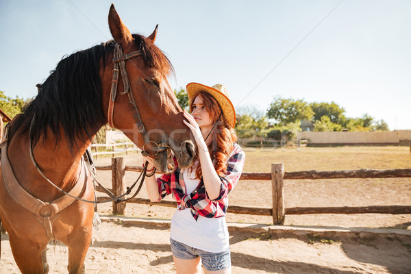Woman cowgirl standing and taking care of horse in village Stock photo © deandrobot