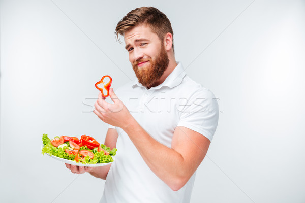 Man holding slice of red papper and plate with salad Stock photo © deandrobot