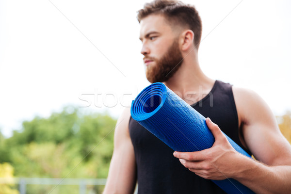 Serious male yoga instructor holding mat and looking away outdoors Stock photo © deandrobot