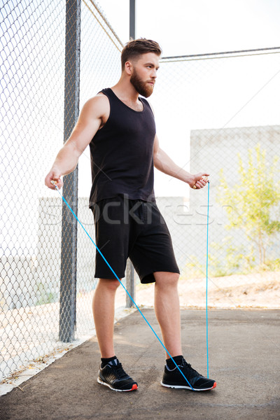 Concentrated fitness man doing cardio exercises with skipping rope outdoors Stock photo © deandrobot