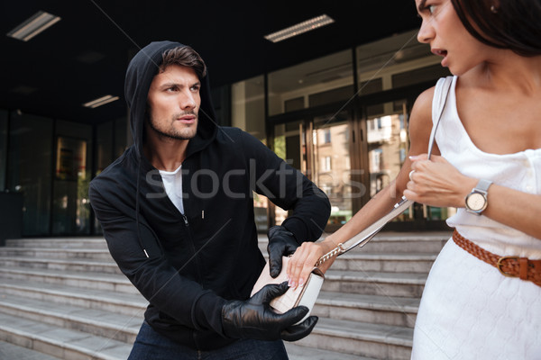 Man thief in black hoodie stealing woman bag Stock photo © deandrobot