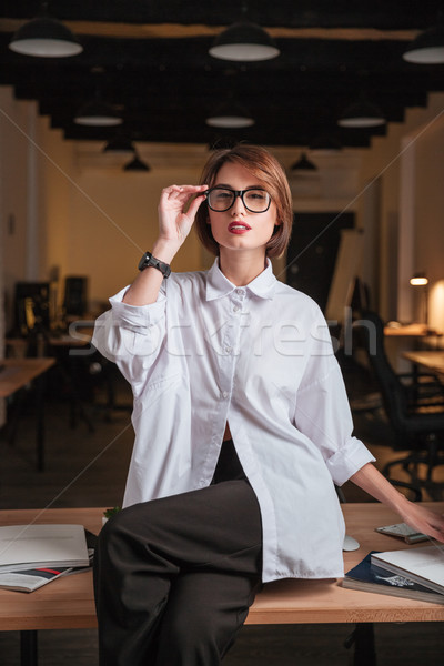 Sensual young businesswoman sitting on the table in office Stock photo © deandrobot