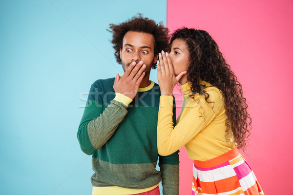 Beautiful curly young woman telling secrets to her boyfriend Stock photo © deandrobot