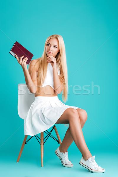 Pensieroso libro seduta sedia Foto d'archivio © deandrobot
