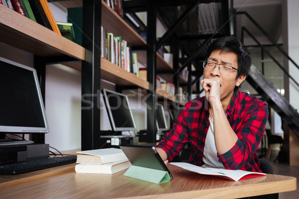 Yawning asian male student using tablet at the library Stock photo © deandrobot