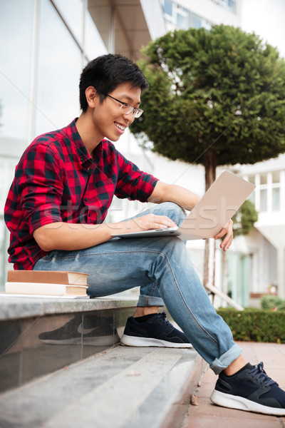 Alegre Asia joven sesión usando la computadora portátil aire libre Foto stock © deandrobot