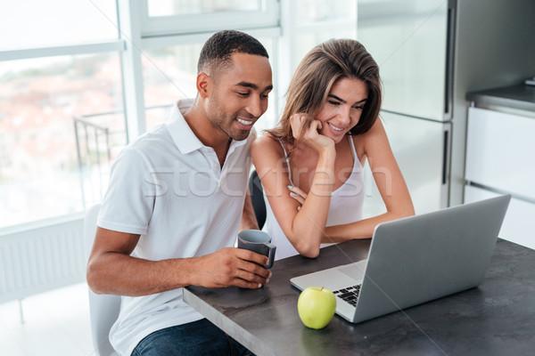 Interracial couple with laptop Stock photo © deandrobot