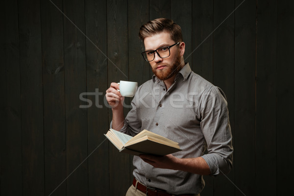 Portrait of concentrated man holding open book and drinking coffee Stock photo © deandrobot