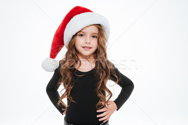 Curly little girl in santa claus hat standing and posing Stock photo © deandrobot