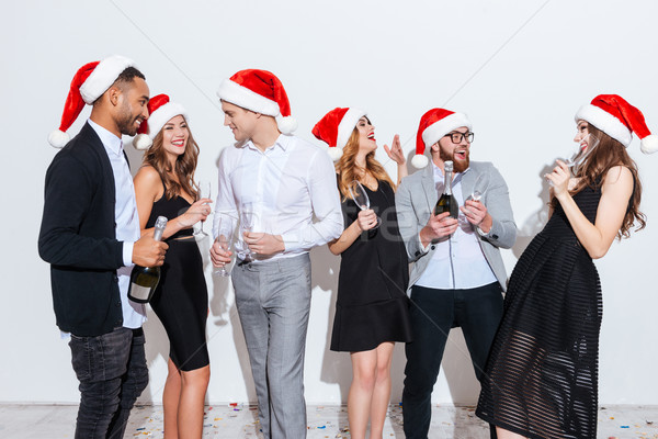 Happy people in santa claus hats drinking champagne and laughing Stock photo © deandrobot