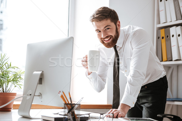 Attractive young businessman drinking tea and using computer. Stock photo © deandrobot