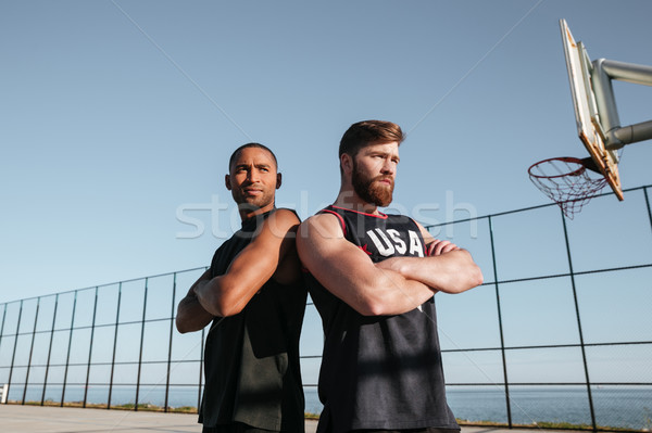 Two basketball players standing at the playgroud with arms folded Stock photo © deandrobot