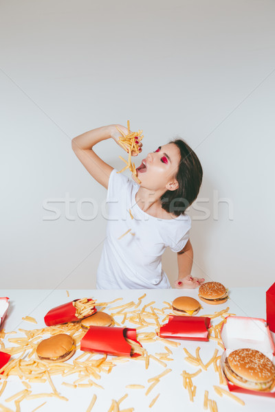 Woman eating french fries at the table with fast food Stock photo © deandrobot