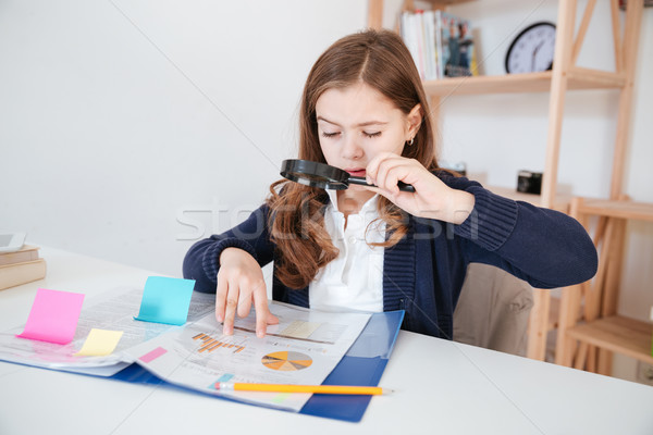 Concentrated little girl reading and looking through magnifying glass Stock photo © deandrobot