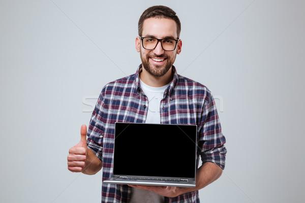 Smiling Bearded man in eyeglases showing blank laptop screen Stock photo © deandrobot
