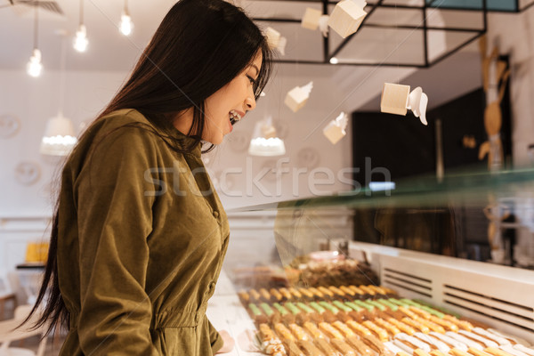 Happy asian young woman standing at the cafe. Stock photo © deandrobot