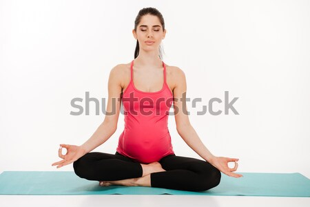 Portrait of a young pregnant woman sitting in lotus position Stock photo © deandrobot