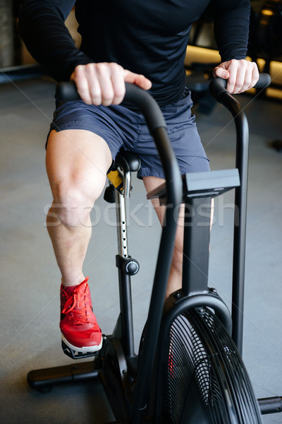 Vertical image of Muscular man using spinning bicycle Stock photo © deandrobot
