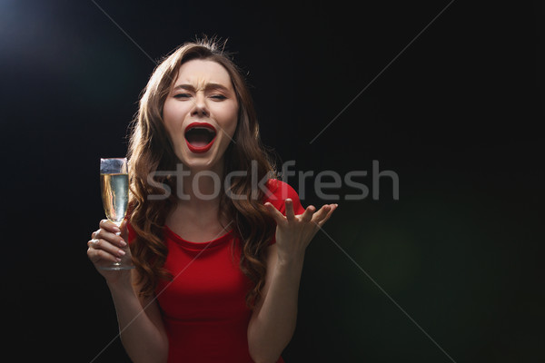 Sad disappointed young woman holding glass of champagne and screaming Stock photo © deandrobot