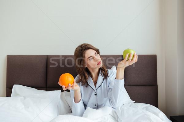 Geconcentreerde jonge dame kiezen oranje appel Stockfoto © deandrobot