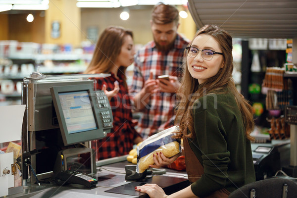 Cashier woman on workspace in supermarket shop. Stock photo © deandrobot
