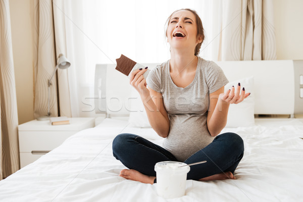 Stock photo: Stressed pregnant woman crying and eating chocolate with ice cream