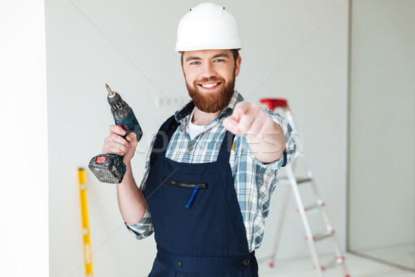 Young man with drill pointing at camera Stock photo © deandrobot