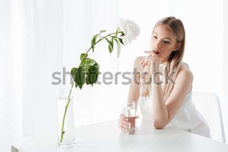 Fashion portrait of a beautiful young redheaded girl sitting Stock photo © deandrobot