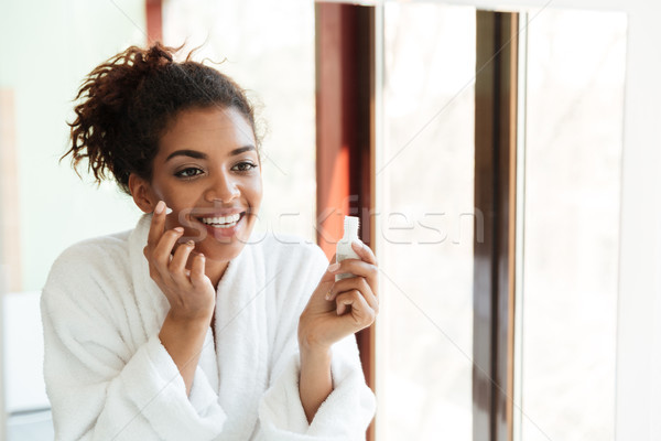 Happy young african lady standing indoors at home Stock photo © deandrobot