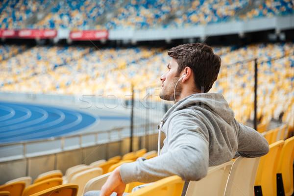 Widok z boku młody człowiek odzież sportowa posiedzenia stadion Zdjęcia stock © deandrobot