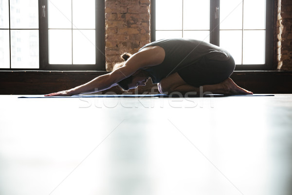 Sporty healthy man stretching back before gym workout Stock photo © deandrobot