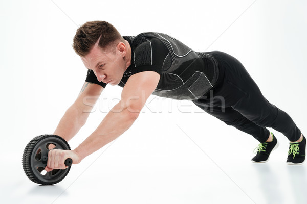 Full length portrait of a healthy athlete man doing exercises Stock photo © deandrobot