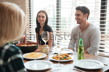 Multiracial young friends enjoying meal while sitting at the dinning table Stock photo © deandrobot