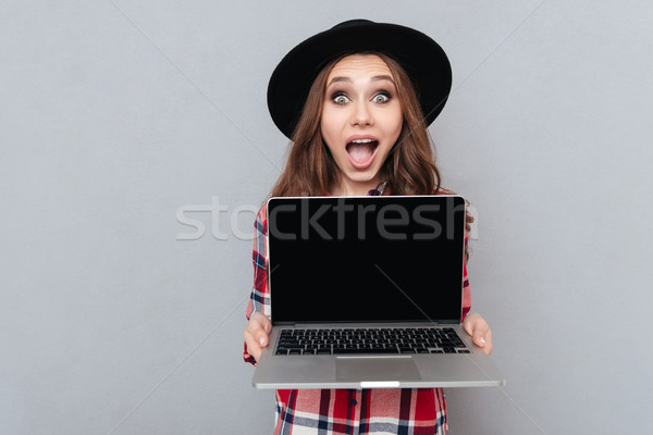 Excited casual girl in plaid shirt holding blank screen laptop Stock photo © deandrobot
