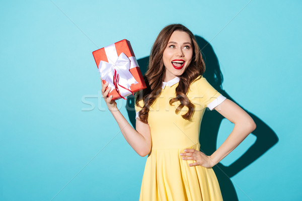 Playful girl in dress holding gift box and looking away Stock photo © deandrobot