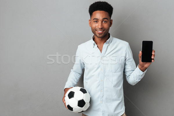 Man showing blank screen mobile phone and holding football Stock photo © deandrobot